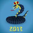 Жёрно-жёлто-красная королевская кобра в короне и надпись 2013. Змея выполнена в технике оригами, фон - голубой