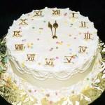 Шикарный новогодний торт в виде циферблата, цифры оформлены при помощи золотой пищевой краски и цветных кондитерских шариков