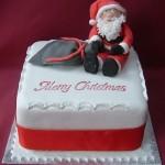 Красивый и вкусный новогодний торт в красно-белых тонах, украшенный марципановым Сантой