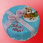 Мишка сидит рядом с новогодней ёлочки на торте, покрытом голубой глазурью