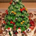 Торт оформлен в виде наряженной ёлочки. Для украшения использовали разноцветную глазурь, пищевые жемчужины. Из марципана или кулинарной мастики вылепили разных животных в новогодних шапочках. Зверушки водя хоровод вокруг ёлки