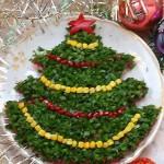 Салату придаём форму ёлочки, посыпаем зеленью и украшаем бусами из моркови, свеклы, кукурузы