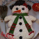 Из сырного салата делаем снеговика, надеваем на него шарф из зелени и цилиндр из маслин
