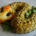 Выкладываем салат на блюдо и придаём форму змеи. Украшаем огурцами, оливками, морковью. Милая змейка украсит ваш стол