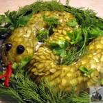 Салат оформлен в виде змеи, спинка выложена огурцами, глаза из маслин. Змея притаилась в укропе