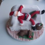 Отмечать Новый год нелегко. Этот новогодний торт оформлен в виде постели на которой Санта отдыхает после ночи подарков и его олень спит рядом с кроватью