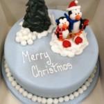 Вкусный и празднично оформленный рождественский торт, покрытый голубой глазурью и украшенный пингвинами из кулинарной мастики, пингвины сидят под ёлочкой