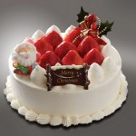 Классный новогодний торт украшенный взбитыми сливками и клубникой. НА торте сидит Санта из кулинарной мастики