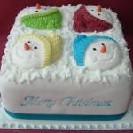 Новогодний торт украшенный снеговиками, одетыми в разноцветные вязанные шапки