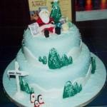 Многоярусный новогодний торт, украшенный ёлочками и Дедом Морозом из кулинарной мастики