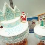 Многоярусный новогодний торт. По белой глазури - новогодний рисунок голубой пищевой краской, торт украшен Дедом Морозом из марципана