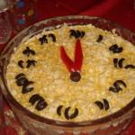 Что может быть проще, чем выложить салат на блюдо, посыпать тёртым сыром, из маслин сделать цифры, а из долек перца - стрелки, которые показывают без пяти двенадцать?
