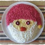 Делаем салат в виде Санта-Клауса: шапка из свеклы, лицо из - яичного желтка, борода из - яичного белка, нос - кусочек моркови, а глаза из оливок.