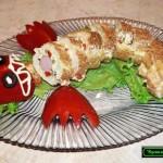 Рулет из ветчины и сыра с чесноком нарезан порциями и выложен в виде змеи
