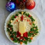 Сырный салат украшенный зеленью в виде рождественского венка и свечкой из сыра и моркови