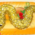 Огурцы использованы для декора салата в виде змеи, а для того, чтобы картинка была ярче добавлены помидорки