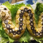 Салат выложен в виде змеи из маслин и маринованых огручиков