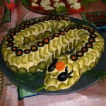 Салат выложен в виде змеи из маслин и оливок. Вместо короны у змеи - морковка, а язык из листика укропа